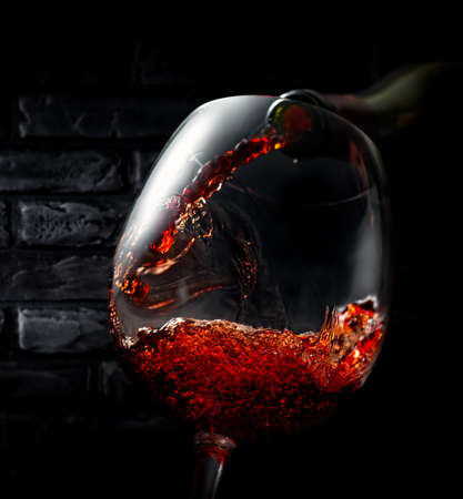 Wine pouring in wineglass on a black background