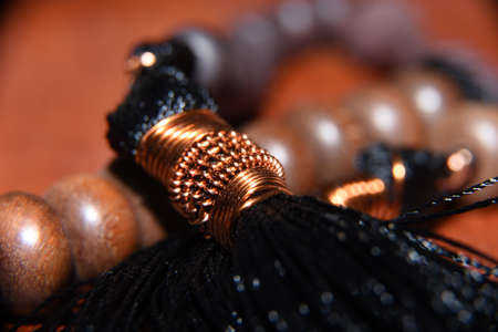 The prayer beads are made of wood in brown with a bundle of black thread tied with a yellow wire as its head