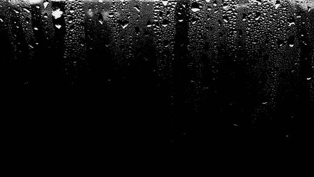 Raindrops on the surface of the window panes with a black background. Natural rain pattern on the glass. Light penetrates through water droplets. Horizontal background for website design Standard-Bild - 129449705