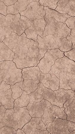 Top view of a lot of crack in the ground. Exposure to heat and drought. Deserts. The effects of global warming. Cracked desert landscape. Brown texture of dry cracked soil. Vertical background Stockfoto