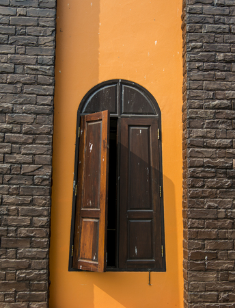 Wooden window on Orange wall photo