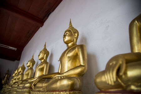 Row of sitting golden buddha statue photo