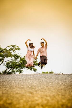 Lovely couple jump on the bridge photo