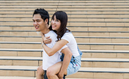 Lovely couple piggy back ride on the stairs photo