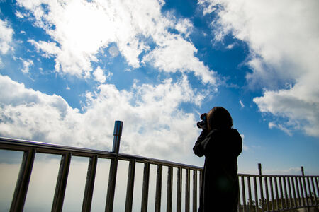 Woman stand near steel fence and take photo blue sky2 photo