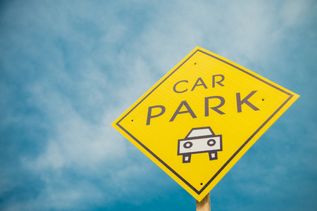 Yellow car park sign with blue sky photo