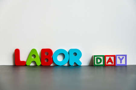 off day: Colorful wooden word Labor day with white background Stock Photo