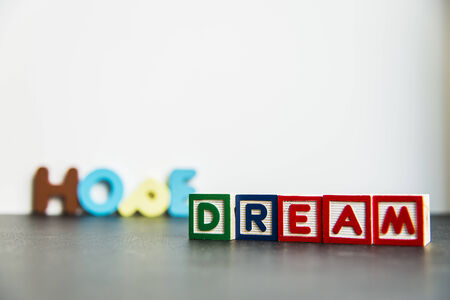 Colorful wooden word Dream and hope on white background