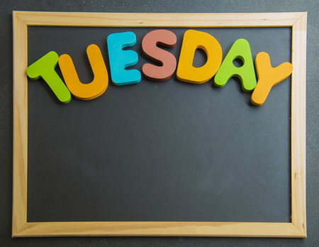 Colorful wooden word Tuesday on black board photo