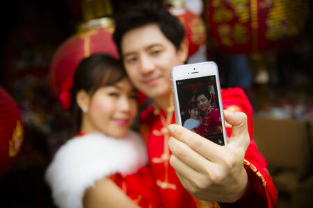 Lovely couple selfie photo by smartphone with red paper chinese lantern in Chinese suit2 photo
