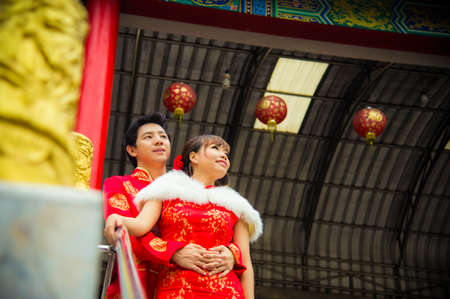 Lovely couple with qipao suit hug in Chinese temple photo