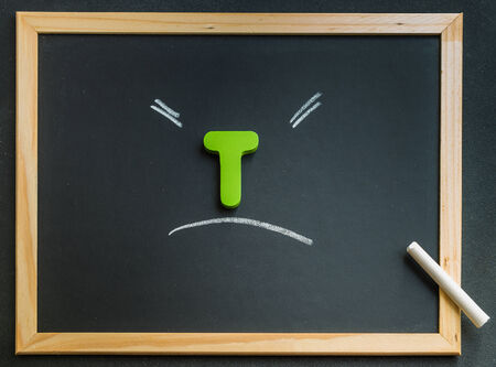 Wooden T character on black board photo