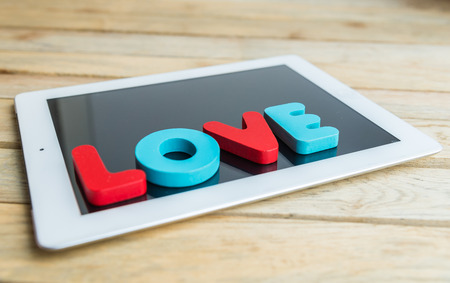 Wooden word LOVE on tablet photo