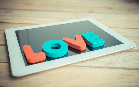 Wooden word LOVE on tablet in vintage style photo