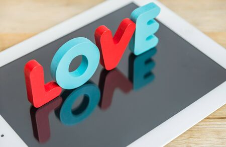 Wooden word LOVE stand on tablet photo