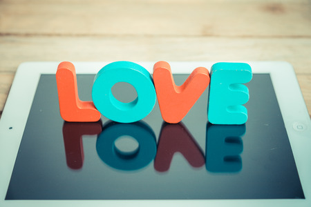 Wooden word LOVE stand on tablet in vintage style photo