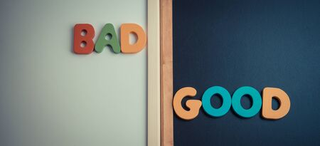 good and bad: Wooden word BAD and GOOD on black board and white board in vintage style Stock Photo