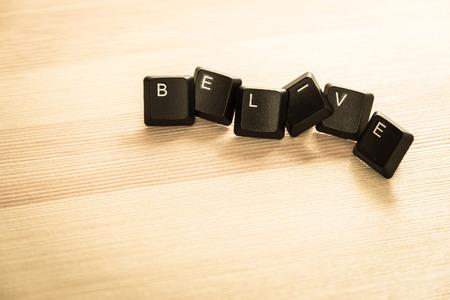 belive: Belive word keyboard on wooden floor in retro style