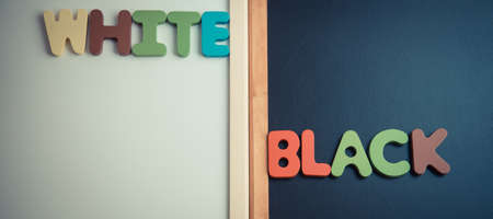 opposed: Wooden word WHITE and BLACK on black board and white board in vintage style Stock Photo