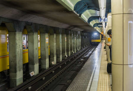 waited: Japanese Subway train is coming in Track with waited passenger