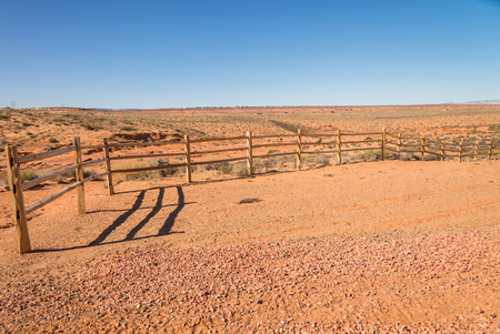 cattle wire wires: Old wooden fence in the sandy desert Stock Photo