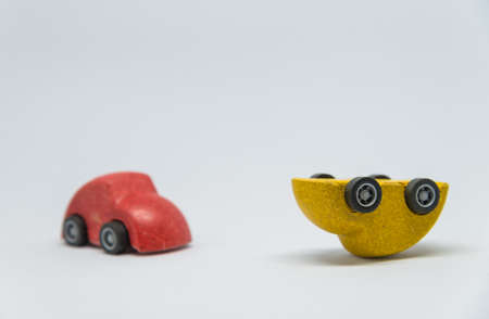 crashed: Red toy car crashed yellow toy car overturned with white background and selective focus Stock Photo