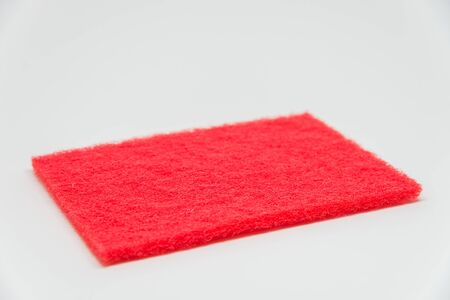 scouring: Red Scouring pad with white background and selective focus