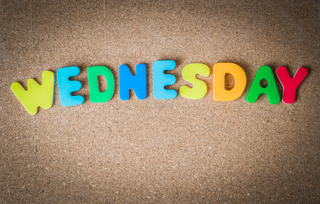 Colorful wooden word WEDNESDAY on Cork board with selective focus Reklamní fotografie