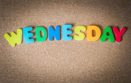 Palabra de colores de madera Miércoles a bordo del corcho con el enfoque selectivo Foto de archivo - 57247323
