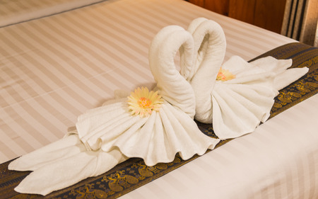 heart suite: White swan from towel in the bedroom with selective focus Stock Photo