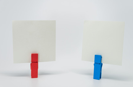 clamped: Piece of Memo paper clamped by red and blue wooden clip with white background and selective focus Stock Photo