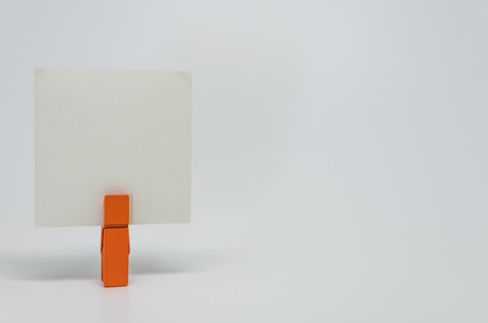 clamped: Piece of Memo paper clamped by orange wooden clip with white background and selective focus