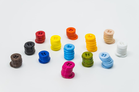 Variety column of colorful button on white background and selective focus