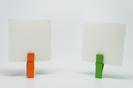 clamped: Piece of Memo paper clamped by orange and green wooden clip with white background and selective focus