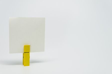 clamped: Piece of Memo paper clamped by yellow wooden clip with white background and selective focus