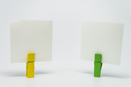 Piece of Memo paper clamped by yellow and green wooden clip with white background and selective focus