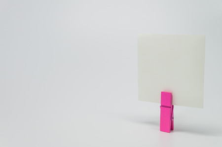 clamped: Piece of Memo paper clamped by pink wooden clip with white background and selective focus