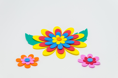 Colorful foam craft flower with green leaf on white background and selective focus Stock Photo