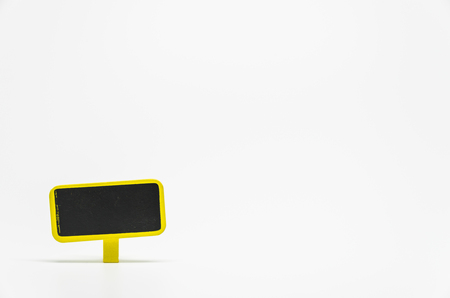 Yellow wooden black board with clip on white background and selective focus Stock Photo