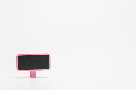Pink wooden black board with clip on white background and selective focus