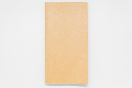 Brown plain notebook on white background and selective focus