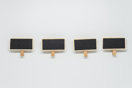 Small wooden black board clip on white background with selective focus