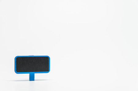 Blue wooden black board with clip on white background and selective focus