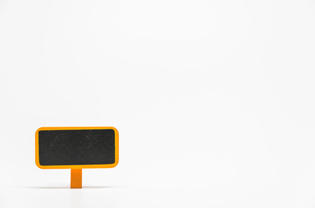 Orange wooden black board with clip on white background and selective focus