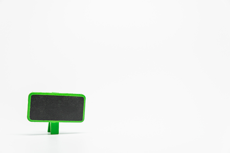 Green wooden black board with clip on white background and selective focus Stock Photo