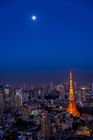 Red Tokyo tower with the moon in the twilight scene and city view