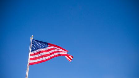 Drapeau américain des USA agitant avec fond de ciel bleu clair en vue horizontale