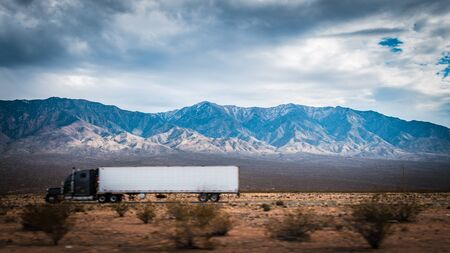 Blur Truck for front object with Beautiful Blue rocky canyon mountain landscape in background with cloudy sky