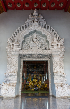 Golden Buddha statue in Wat Ming Muang which decorate by white cement carvings in Northern Thai style in Nan Thailand Banque d'images