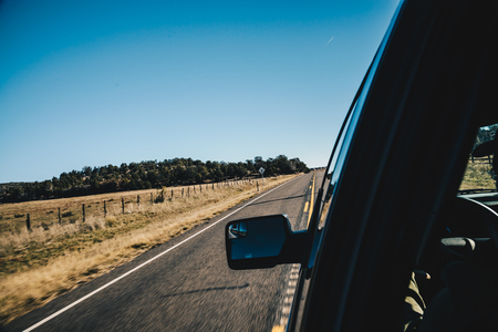Motion blur view of road with side mirror from inside car